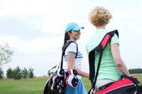 Popular : Smiling female golfer talking to friend at golf course