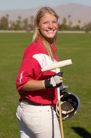 Smiling female polo player standing on polo field holding polo stick and helmet side view