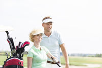 Popular : Smiling golfers standing at golf course against clear sky