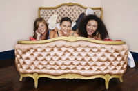 Smiling teenage girls lying on funky cushion bed