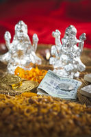 Snacks and money in front of idols of lakshmi and ganesh during diwali festival
