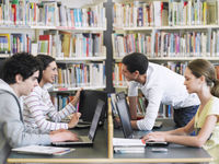 Students using laptops in library