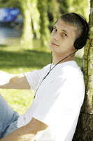 Teenage boy leaning against tree listening to music on the headphones