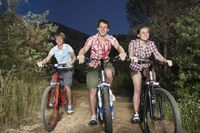 Popular : Teenage boys and girl  16-17 years  riding bikes on country road in evening