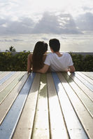 Popular : Teenage couple  16-17  sitting on wooden deck looking at view back view