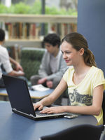 Teenage girl using laptop in library