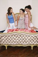 Popular : Teenage girls at slumber party kneeling on funky bed