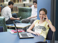 Teenage using mobile phone sitting in library