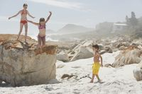 Three children playing on rocky beach