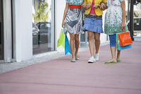 Popular : Three teenage girls  16-17  carrying shopping bags walking on street low section