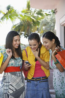 Popular : Three teenage girls  16-17  on street holding shopping bags and text messaging