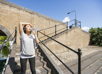Tired young woman drinking water on stairs