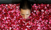 Top view of a woman bathing in a bathtub of flower petals