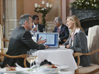 Two business people having conversation at restaurant table with laptop