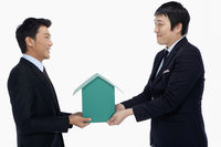 Popular : Two businessmen holding a cardboard house