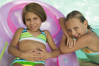 Two girls  7-9  in swimming pool portrait