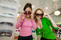 Two girls trying on sunglasses in boutique portrait