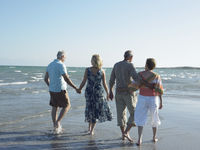 Two senior couples walking on beach back view