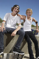Popular : Two teenage boys  16-17  with skateboards at skate park portrait