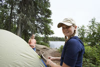 Two teenage girls standing by tent near lake portrait