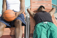 Two young man relaxing on sunlounger one with basketball