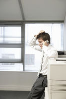 Uncertain businessman leaning on office photcopiertalking on cell phone