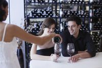 Waitress pouring wine for man and woman at the bar