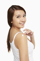 Popular : Woman applying lotion on her shoulder