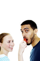 Woman feeding her boyfriend a strawberry