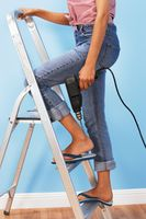 Woman holding power drill on stepladder low section