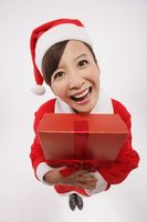Woman in santa suit hugging her present