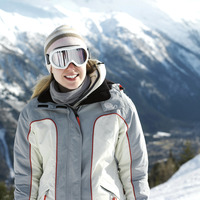 Woman in warm clothing and ski goggles smiling