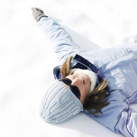 Woman in warm clothing and sunglasses lying down on snow