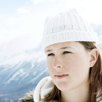 Woman in white knitted hat in deep thought