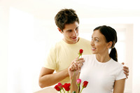 Woman looking at her boyfriend while holding a rose