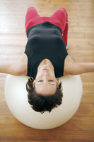 Woman lying with her back on fitness ball