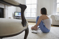 Woman sitting on floor watching television back view