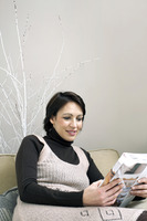 Woman sitting on the couch reading magazine