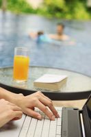 Woman using laptop by the pool