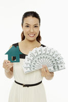 Woman with a paper house and cash