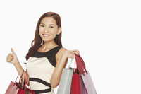 Woman with shopping bags showing hand gesture