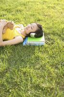 Woman with teddy bear lying on the grass listening to music