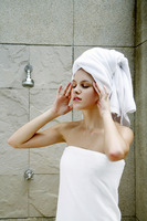 Popular : Woman with towel wrapped hair massaging her head in the bathroom