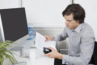 Young businessman using hole puncher at desk