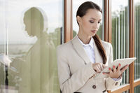 Young businesswoman using digital tablet against office building
