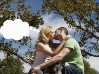 Young couple kissing with think bubble above woman s head