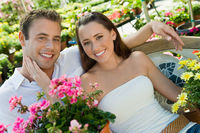 Young couple sitting on bench in garden centre  portrait