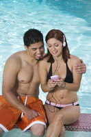 Young couple with mp3 player relaxing at swimming pool