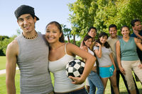 Young couple with woman holding soccer ball group of friends in background