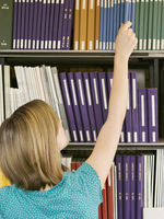Young girl reaching for book from library shelf back view